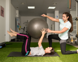 A Physical Therapist helping someone with core work